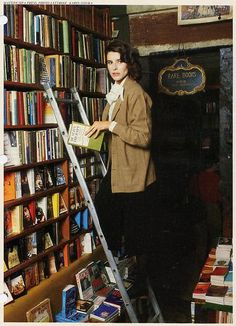 French actress Fanny Ardant reading in bookshop. Photographed for French Vogue in 1979.