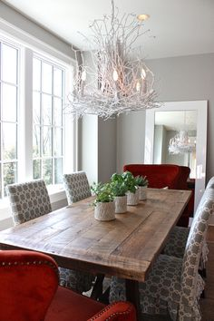 GASP! This is perfection. I love the rough, though polished, table, the mix of shapes and fabrics of the chairs, and the white branch-y chandelier.