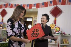 China's First Lady Peng Liyuan (R) smiles as US First Lady Melania Trump (L) holds up Chinese calligraphy of the character 'Fortune' written by a student during a visit at Banchang Primary School in Beijing on November 9, 2017.
