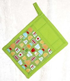Handmade pot holder featuring a designer fabric of festive kitchen icons and fruit and a coordinating green fabric to add fun to your kitchen. 6.5 x 9, with a 2 hanging loop. All our products are made from high quality designer fabrics for uniqueness and durability. Custom edge binding and a functional hand pocket set our products apart from the rest. The large front hand pocket is easy to use and more versatile than an oven mitt. The custom edge binding ensures that your potholder will hold…