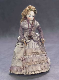 French Bisque Poupee, wearing a costume of mauve silk and lace, undergarments,leather slippers,gilt opera glasses. Circa 1865