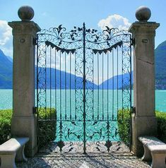 On the promenade in Lugano, Switzerland an ornate gate showcases beautiful Lake Lugano