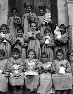 Large group of girls holding their dolls.