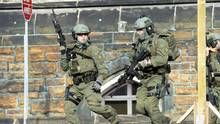 An RCMP intervention team run next to a Parliament building in Ottawa Wednesday Oct.22, 2014. A Canadian soldier standing guard at the National War Memorial in Ottawa has been shot by an unknown gunman and there are reports of gunfire inside the halls of Parliament. THE CANADIAN PRESS/Adrian Wyld (Adrian Wyld/THE CANADIAN PRESS)