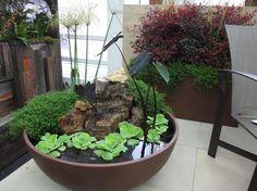 idée de décoration de terrasse - petit bassin aquatique décoré de plantes aquatiques et roches