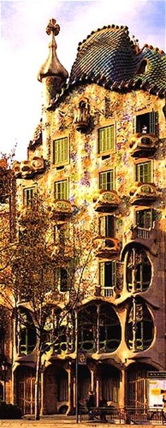 Casa Batllo, Barcelona.  Architect: Gaudi.  In some pictures this building is bright blue, others are more yellow and some are white underneath the multi coloured designs.  One day I'll go and see which one is the actual colour :)