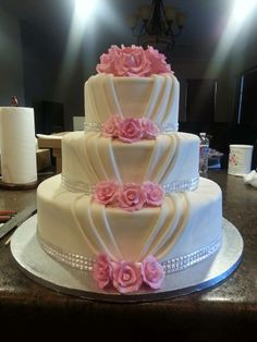 A beautiful pleated white wedding cake with bling and roses.