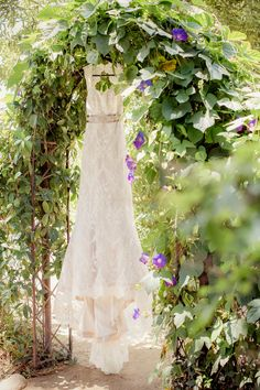 Classic Lace Wedding Dress hanging in a Flowering Arbor | Figlewicz Photography | See More! http://heyweddinglady.com/classic-garden-wedding-in-rich-purple/