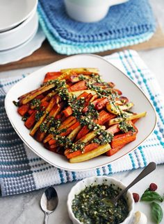 Simple, colourful, and delicious! This root vegetable dish featuring carrots, parsnips, and sweet potatoes is topped with a fresh basil pesto!
