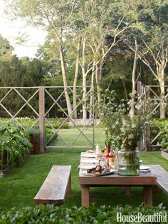 Rustic Dining Area - 10-foot-long table sits in the center a vegetable and cutting garden. The Belgian oak furniture, Tuscan stoneware, handblown goblets, vase, and linen napkins all set the scene. A graphic cedar deer fence encloses formal raised planting beds.