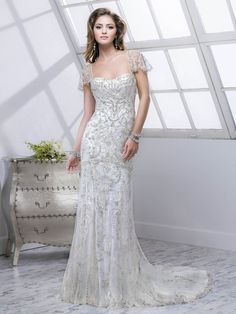 Sottero and Midgley - LOLA, Intricate patterns of Swarovski crystals and mirrored beads adorn this tulle over Valentina Satin, slim A-line gown.  Finished with zipper over inner elastic closure.