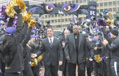 Baltimore Ravens coach John Harbaugh, left, and Ozzie Newsome, right, greet the crowd.