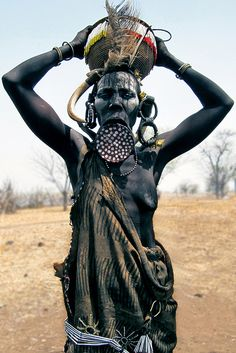 Mursi woman with wild boar's tusks and ornamental clay lip-plate Most Mursi women wear lip-plates as an aesthetic symbol of cultural pride and identity, signifying passage to womanhood. Mursi settlement near Mago River in southern Ethiopia's lower Omo Valley.
