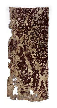 Brunrött mönster på vitmålad botten.