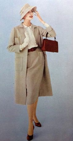 1957 Model in sand-beige wool skirt and silk shirt worn under straight line coat by Norman Norell