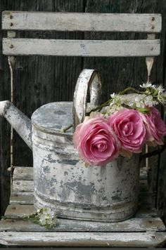 Galvanized watering can with pink roses on a French bistro chair