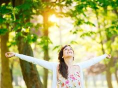 Blissful woman enjoying freedom and life in park on spring.