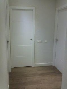 Puertas lacadas blancas estilo moderno y suelos de tarima en roble.