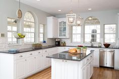 Beautiful hardwood floors and granite countertops bring this fabulous kitchen into the 21st century. The original lower cabinets were painted a bright white, enhanced by the natural light from the large windows.