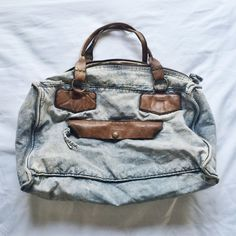 free people leather / chambray bag this bag is amazing!! u can wear as larger everyday bag or an overnight bag! it's such a cute bag ... hate to get rid of it! small pink/red stains as shown in pictures. I think I spilled Gatorade on it  still a lovely bag by free people !! OFFERS ALWAYS WELCOME  Free People Bags Shoulder Bags