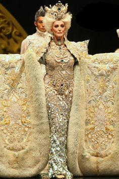 """On a Beijing runway, legendary American model Carmen Dell'Orefice strutted in an extraordinary gown by Guo Pei, China's """"Empress of Haute Couture,"""" which was so heavily embroidered that four men had to assist her."""