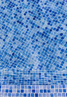 Background texture and abstract geometric pattern of blue mosaic tiles in a swimming pool viewed through clean clear water