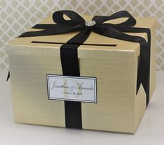 """Wedding Card Holder Box Champagne Gold and Black Classic Customizable. This Card Box is big enough to hold around 200 cards. The slot is big enough for those unusually shaped cards. You can be assured that the cards, gift cards and money inside are secure and not easy to open. Customize your Card Box by selecting your choice of Box Fabric Color and Ribbon Color. Personalized by adding the Name Tag to your Card Box. Card Box measures: 11x11x7"""" We hand make with care using only the finest..."""