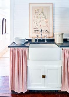 modern farmhouse kitchen with curtained kitchen sink. #sink #kitchensink #cabinetry #whitecabinets #artwork #poster #art #kitchen #kitchendecor #farmhouse #kitchendesign #vintagefaucets #curtains #curtainedsink