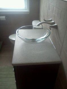 Wonderful Solid Surface Counter With Clear Vessel Sink Bowl And Wall Mount Faucet.