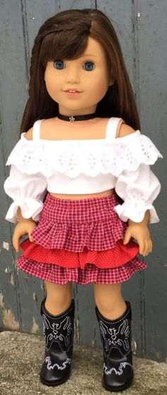 This top is made from a woven cotton with white-on-white pin dot print. It has a ruffle around the neck and elasticized sleeves; they can be pushed up or pulled down to vary the length of the sleeve. The bodice is lined with white cotton batiste and closes in the back with Velcro. The top comes with the black satin ribbon choker. It has a silver flower bean sewn onto it, and it closes in back with a snap. The skirt is made of a woven cotton plaid and polka-dot fabrics; it pulls on with an…