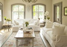 White couches are a true classic, and look simply lovely paired with garden-style accents like a floral rug and sage trim. Choose white slipcovers to make this look more practical (and easier to clean). #Light&Airy #WhiteLivingRoom