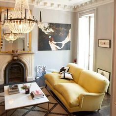 chic modern french yellow & gray living room design with gray wall paint color, crown molding, stone fireplace, crystal chandelier, French brass marble coffee table, yellow velvet sofa, gold gilt mirror   -decorpad