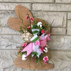 This Easter door hanger is made of wood. Item has been stained and a ribbon mix with greenery and flowers added. Technically, this hanger could be used all spring and summer! Item measures 22 inches Ribbon and greenery may vary depending on stock, but will still be super cute! We