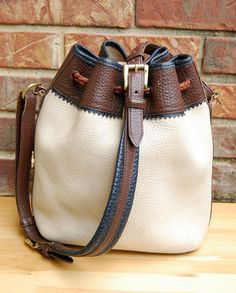 """This gorgeous pebbled leather bucket bag is a rare Dooney & Bourke Teton design. It has some damage which is reflected in the low price (please read below for the wear!***)    Features:  • Cream colored leather exterior; navy blue and dark brown trim  • Brown leather cord closure with cream pebbled leather tassels  • Classic unlined leather interior  • Solid brass hardware, buckles, & original duck hang tag    Measurements:  • 48"""" adjustable leather strap (19"""" drop, 5 notches)  • 11"""" width x…"""