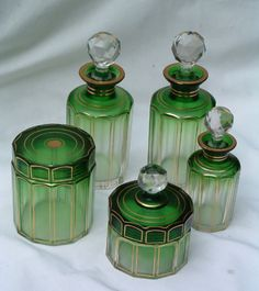 A Green Gilt Baccarat Dresser. French: Pre The five piece set of green to clear glass, with fine gilt and faceted sides, and clear fluorescing stoppers.