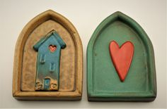 Home is Where the Heart is by Cathy Broski. These thick deep-set tiles are fashioned after doorways, windows, and shrines. Each is pulled one at a time from original molds made by the artist. The center image is individually made and placed in the tile after both are glazed.