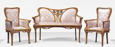 JEAN CANEPA A THREE-PIECE SALON SUITE, 1900 carved walnut and upholstery, comprising sofa and two open armchairs, the back of the sofa centred by carved and pierced irises, the frames elaborately carved with stylised flowing foliage sofa 39 in. (99 cm.) high; 55.1/8 in. (140 cm.) wide; 22.1/8 in. (56 cm.) deep; armchairs 37.3/8 in. (95 cm.) high