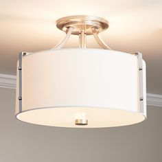 The Highfield Ceiling Light Fixture features a fabric drum shade and metal accents to give it a modern look. This product has a Semi-Flush-Mount design that makes it perfect for a living or dining room with a low ceiling. Designed to accommodate three bul