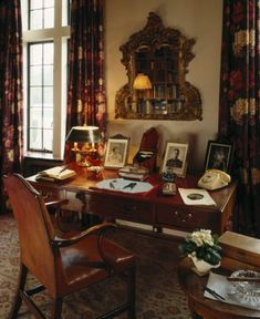 View of Churchill's desk in the Library at Chartwell. On the desk are three framed photos, a telephone, a desk lamp, a writing pad and a few other objects. Above the desk is a mirror.