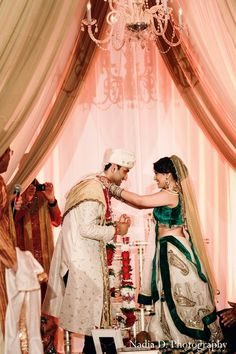 This Indian bride and groom celebrate their marriage in a traditional ceremony with beautiful peaches and cream decor.
