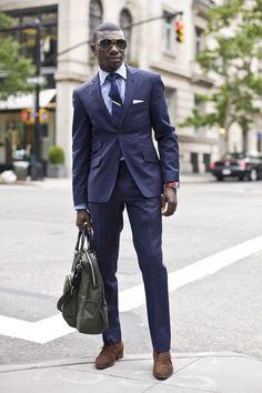Navy suit, blue plaid shirt, navy tie, brown shoes. Accessories orange watch, shades.