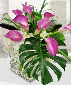 """A premier design that only the artisans at Beneva Flowers can create! Nestled into a 6"""" cube are white hydrangea with wonderful purple calla lilies! Deluxe greens offer dimension and texture to this truly lush arrangement. #benevaflowers #hydrangea"""