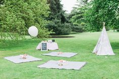 A cute kitty cat party for a first birthday celebration with a picnic in the park, tipi full of toys, cake and cat decorations.
