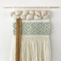 This is a woven wall hanging that was handmade in Minneapolis, MN. This wall hanging is made from 100 % wool roving, 100% wool yarn, and gold glitter yarn. Colors: white/ivory, mint, and gold. This wall hanging is 10 inches wide, 20 inches long, and hangs on a 12 inch wooden dowel.
