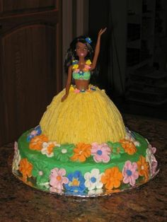 hula barbie - I made this for a girl at work.  Her child was turning 13 and they were having a hula themed party.  I made the flowers out of fondant and the small ones around her skirt and neck out of royal icing