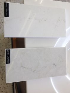 Vanity Countertop: Caesarstone 'London Grey' vs. 'Frosty Carrina (top)' - Frosty Carrina is much whiter background with very slight grey veining. London Grey has a cooler gray background with slight warm tan and grey veining.