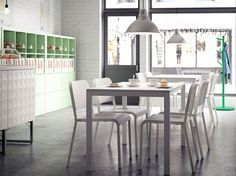 A café with white chairs and small tables together with light green shelving units