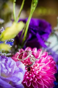 Wedding rings on purple and pink bouquet of flowers.