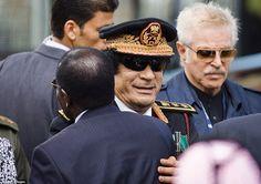 Old dictators club: President Mugabe embraces Libyan leader Muammar Gaddafi at the inaugur...