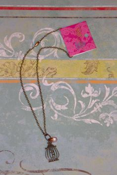 """Tess"" bronze bird cage in many colors  Color options:  Peach Tan Light Pink Teal  Fuchsia   simple delicate silver chain and arrow necklace about 17 inches  Material:Alloy"